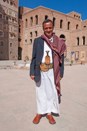 A yemeni man wearing a belt with the ornate knife called janbiya in front of the National Museum of Yemen, the Old City of Sana'a, traditional costume, daily life