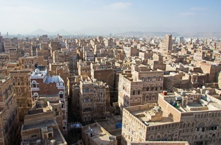 The Old City of Sana'a, decorated houses, palaces, minarets and the Saleh Mosque in the fog, Yemen