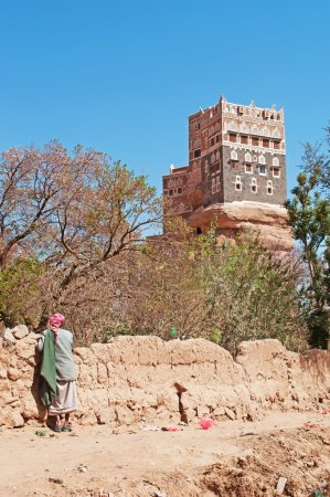 A yemeni man watches the Dar al-Hajar, Dar al Hajar, the Rock Palace, royal palace, iconic symbol of Yemen