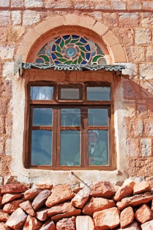 An old yemeni man behind a window in a decorated old house, Kawkaban, the ancient walls, Yemen