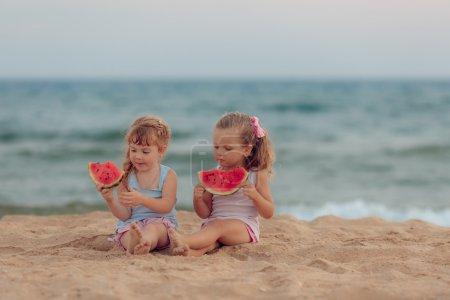 Photo pour Deux belles filles mangeant de la pastèque mûre sur la plage - image libre de droit