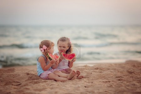 Girls eating ripe watermelon on the beach