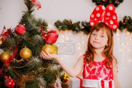Photo pour Adorable fille aux cheveux roux dans une pièce près du sapin de Noël . - image libre de droit