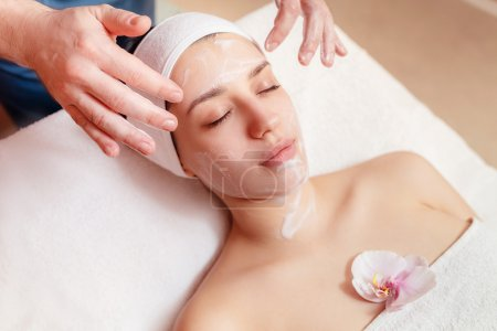 Applying facial mask at woman face