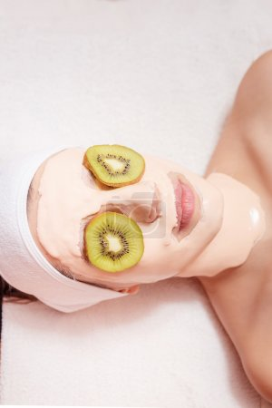 Woman with facial mask of kiwi slices