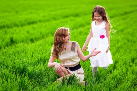 Photo for Happy mother and daughter enjoying time together on the green field - Royalty Free Image