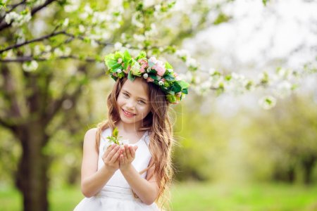 Toddler girl in blooming cherry garden