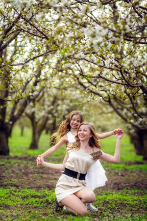 Woman with  daughter  have fun  in the garden