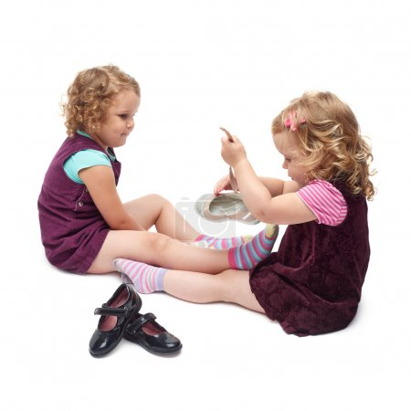 Couple of young little girls sitting over isolated white background