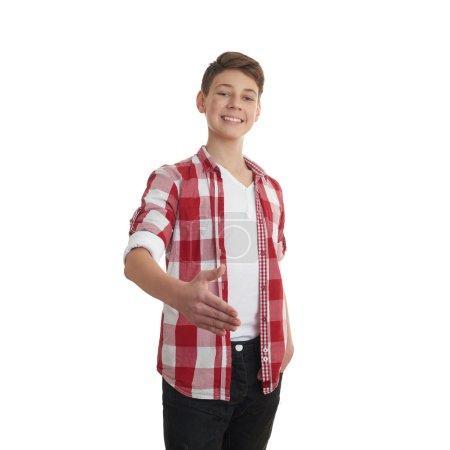 Foto de Lindo adolescente chico en rojo a cuadros camisa estiramiento mano en saludo sobre blanco aislado fondo, medio cuerpo - Imagen libre de derechos