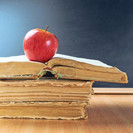 Photo for Red apple lying over a pile of old books against the blackboard background as a back to school composition - Royalty Free Image