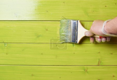 Process of painting the pine wood boards with the brush and the green paint