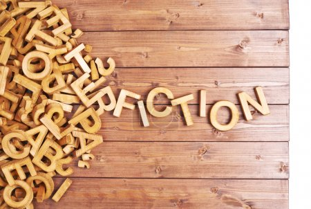 Word fiction made with block wooden letters next t...