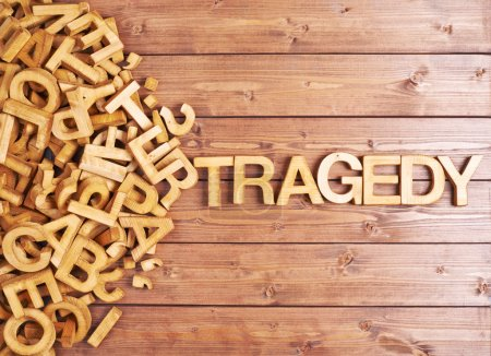Word tragedy made with block wooden letters next t...