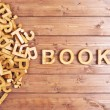 Word book made with block wooden letters next to a...