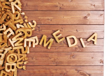 Word media made with block wooden letters next to ...