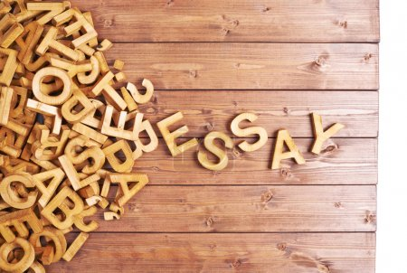 Word essay made with block wooden letters next to ...