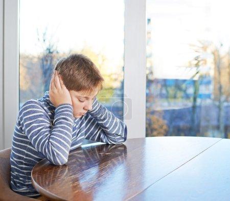 Photo pour Garçon triste de 12 ans s'asseyant au bureau en bois avec ses oreilles de couverture de main, composition contre la fenêtre - image libre de droit