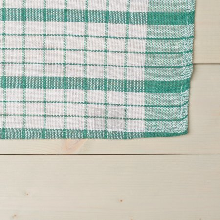 Photo for Green squared tablecloth or towel over the surface of a wooden table - Royalty Free Image