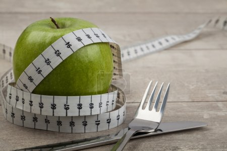 Measuring tape and green apple