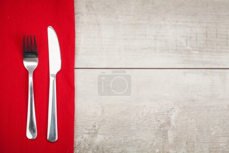 Photo for Fork and knife of iron on the background made from tablecloth on wooden table - Royalty Free Image