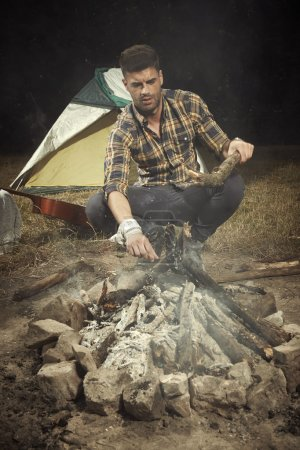 Man relaxing with fire and guitar in summer camp