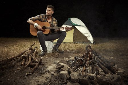 Man in camp playing on accoustic guitar with fireplace