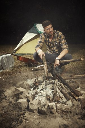 Man chilling out in camp with guitar