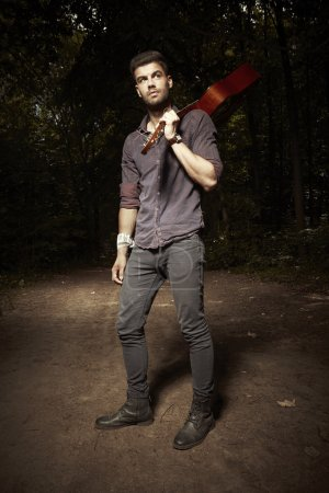 Man with accoustic guitar in forest