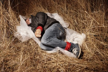 Photo for Murdered man left in winter grass by criminal after hitch-hiking - Royalty Free Image