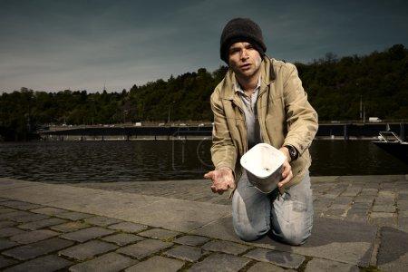 Photo pour Jeune mendiant laid demandant des pièces sur la rive de la rivière de la ville - image libre de droit