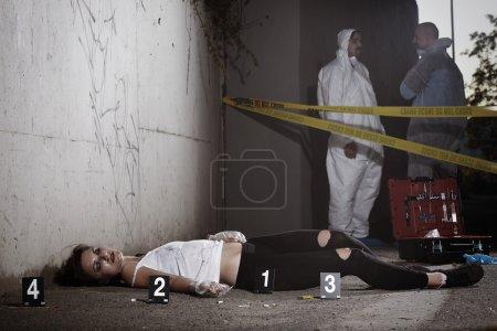 Technicians on crime scene near body of drug victim