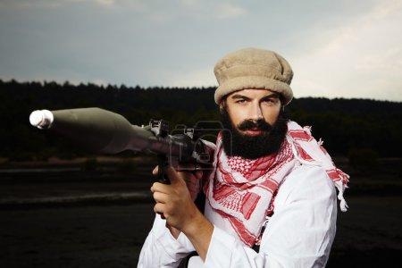 Photo pour Homme au gilet d'explosifs, se présentant comme un combattant sur fond noir - image libre de droit