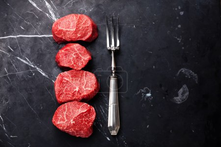 Photo for Raw fresh marbled meat Steaks filet mignon and meat fork on dark marble background - Royalty Free Image