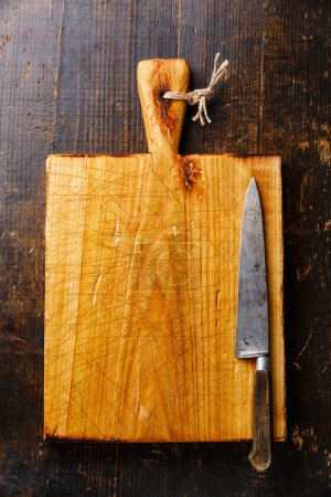 Photo for Chopping board and kitchen knife on dark wooden background - Royalty Free Image