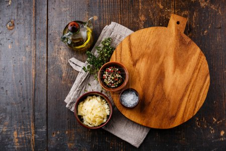 Photo for Cutting board, seasonings and parmesan cheese on dark wooden background - Royalty Free Image