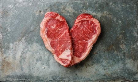 Photo for Heart shape of fresh meat Steaks on stone slate background - Royalty Free Image
