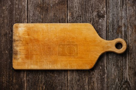 Photo for Empty vintage cutting board on dark wooden background - Royalty Free Image