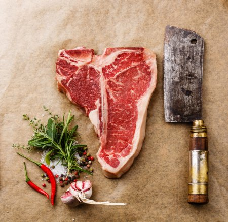 Photo for Raw fresh meat T-bone steak, seasonings and Butcher cleaver on cooking paper background - Royalty Free Image