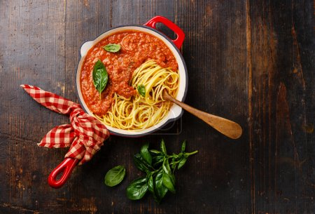 Photo for Spaghetti Bolognese with tomato sauce and basil in iron pan on wooden background - Royalty Free Image