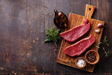 Raw fresh meat Striploin steak and seasoning on da...