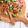 Ingredients of Fresh vegetable salad on olive wood cutting board
