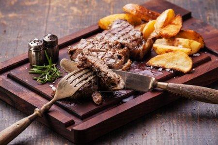 Photo pour Steak New York grillé bien cuit et tranché avec quartiers de pommes de terre rôties sur planche à découper sur fond bois foncé - image libre de droit