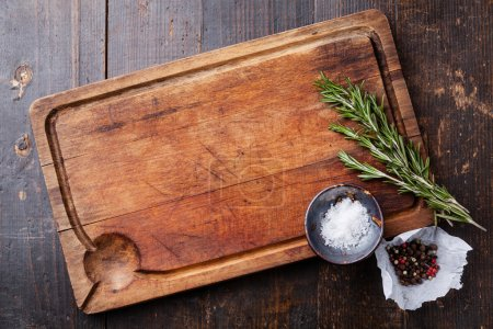Photo for Chopping board, seasonings and rosemary on dark wooden background - Royalty Free Image