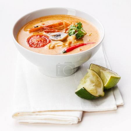Photo for Spicy Thai soup Tom Yam with Chili pepper and lime on white background - Royalty Free Image