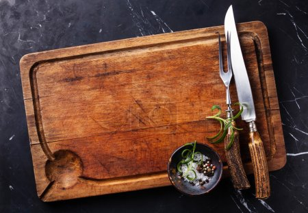 Photo for Chopping cutting board, seasonings and rosemary with fork and knife carving set on dark marble background - Royalty Free Image