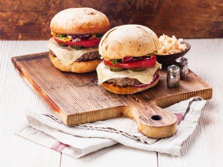 Photo pour Burgers à la viande et salade de chou sur planche à découper sur fond bois - image libre de droit