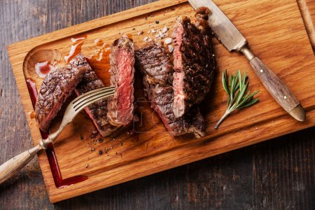 Photo for Sliced medium rare grilled Beef steak Ribeye with rosemary on cutting board on wooden background, close up - Royalty Free Image