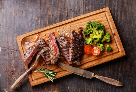 Photo for Sliced medium rare grilled Beef steak Ribeye with broccoli on cutting board on wooden background, top view - Royalty Free Image