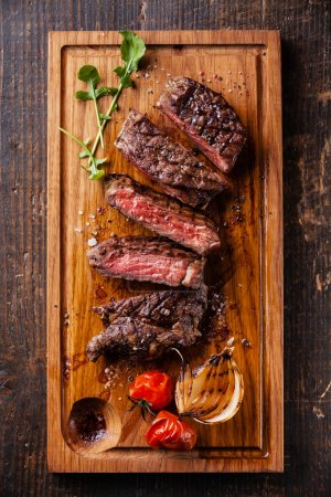 Photo for Sliced medium rare grilled Beef steak Ribeye with grilled onions and cherry tomatoes on cutting board on wooden background, top view - Royalty Free Image